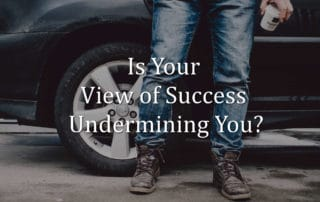 legs of a man in jeans standing in front of a car