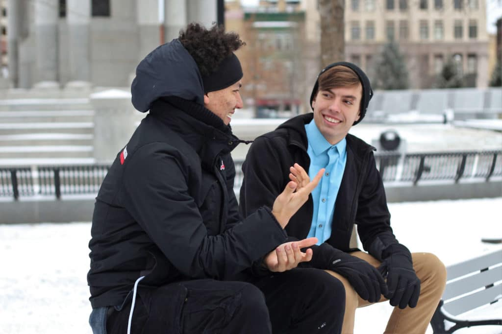 2 men talking on a bench