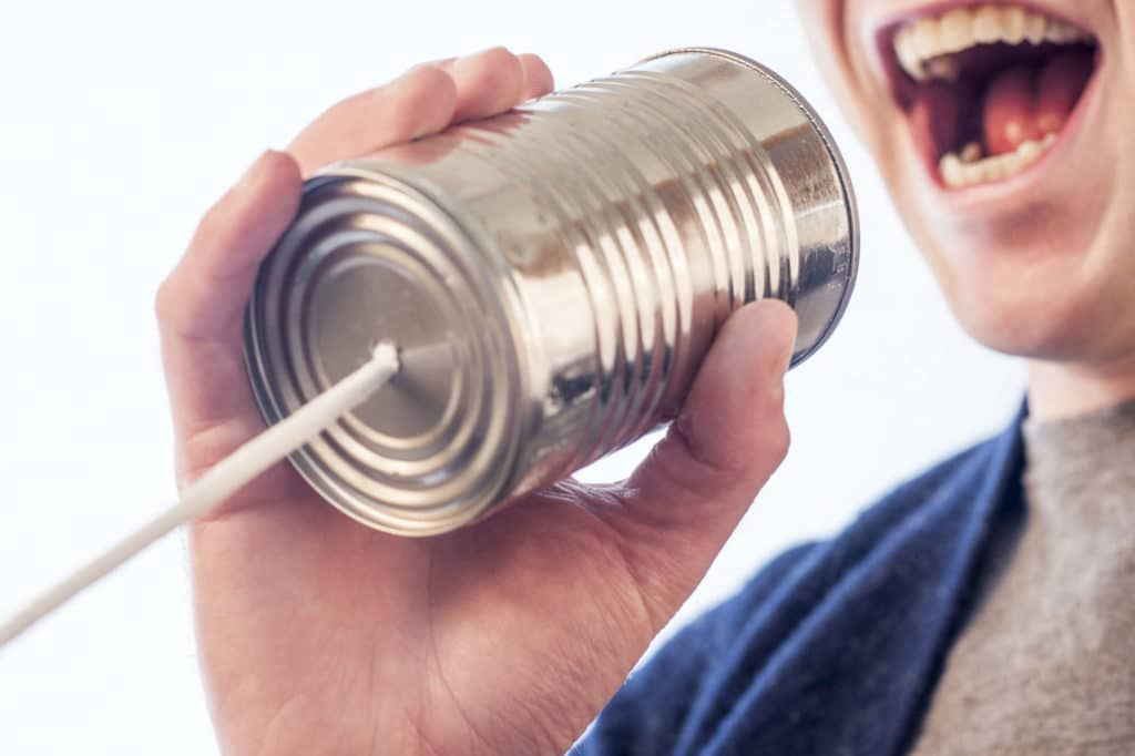 person speaking into a can with a string