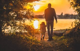 Sunset walk near lake, man holds child hand