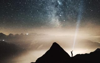 Time Management Tips - Person on mountain with light shining into sky