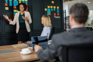 conflict resolution skills - people talking in meeting, woman presenting