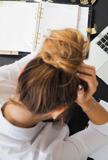 poor time management habits - woman leaning on desk stressed