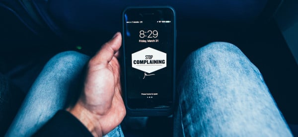 take personal responsibility - man holding phone that says stop complaining