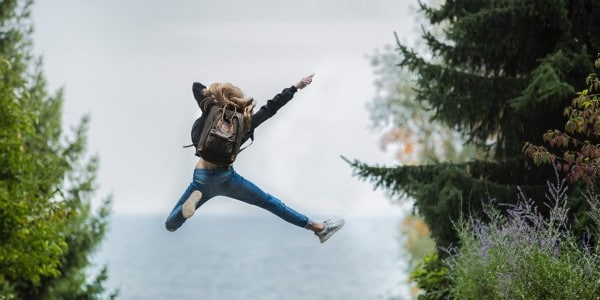benefits of time management - woman jumping in air near trees