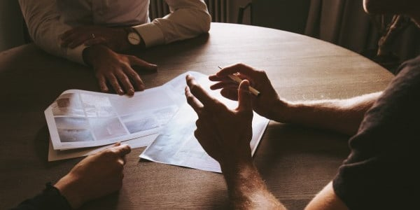 benefits of time management - people meeting around a round table, just see hands and paper and table
