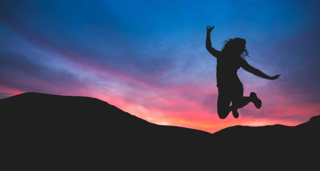 benefits of time management - woman jumping in sunset