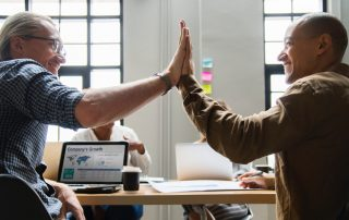 importance of time management - two men giving high five in office