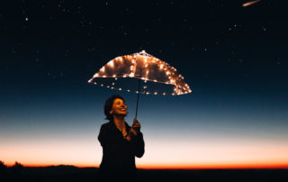 benefits of goal setting - woman holding umbrella that has lights against the night sky