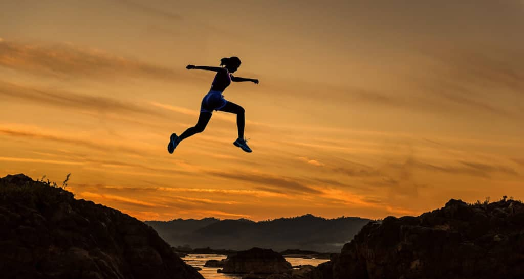 how to set goals - woman jumping over ravine