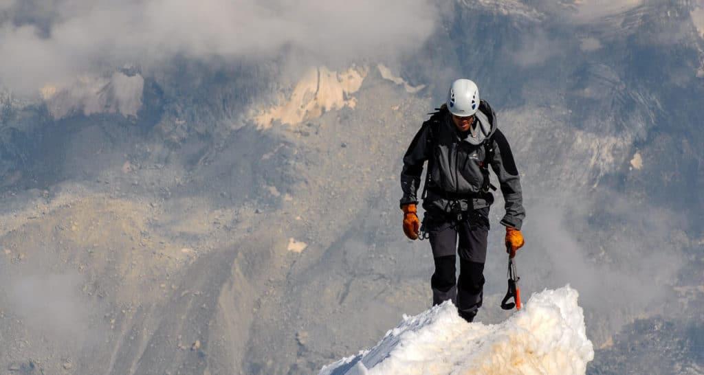 stretch goals - man ice climbing, on top of ice summit