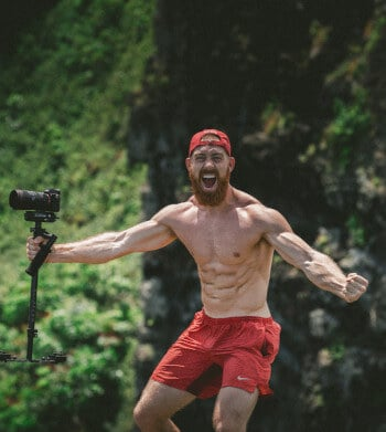 The Definitive Guide to Goal Setting - muscular man holding camera excited